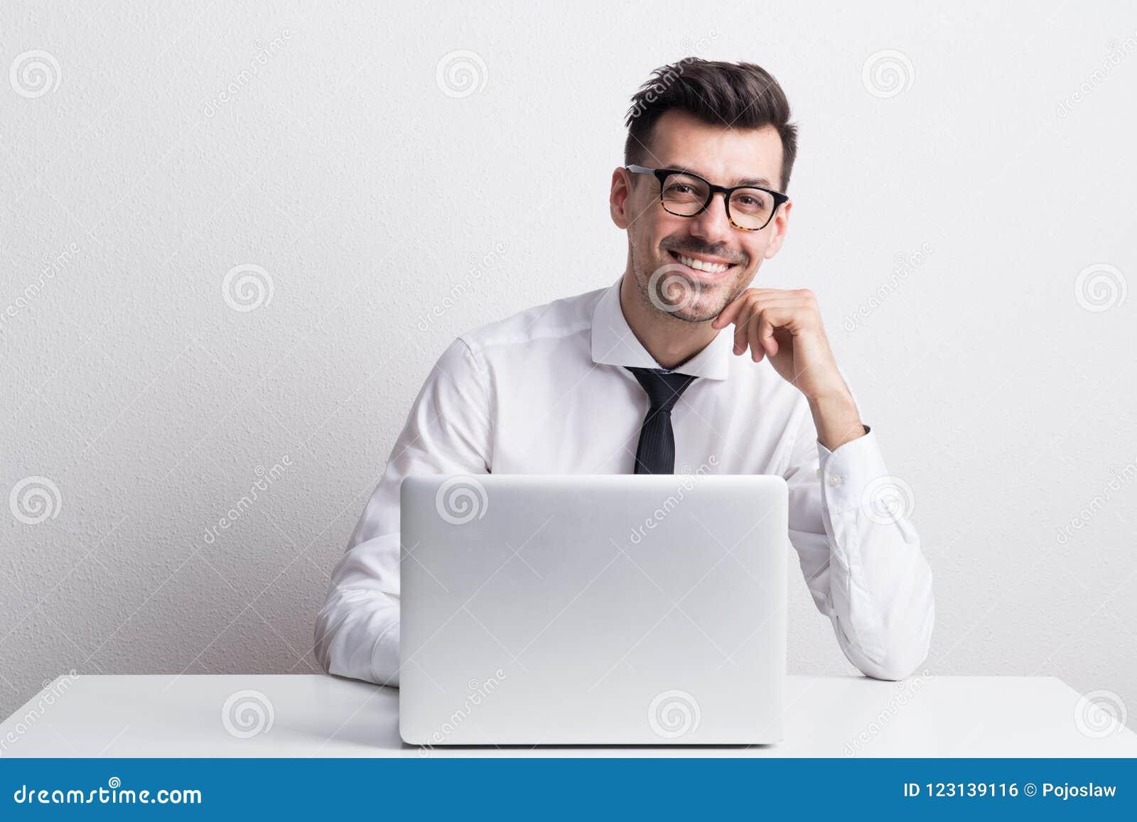 Portret młody człowiek z laptopem w studiu, pracuje