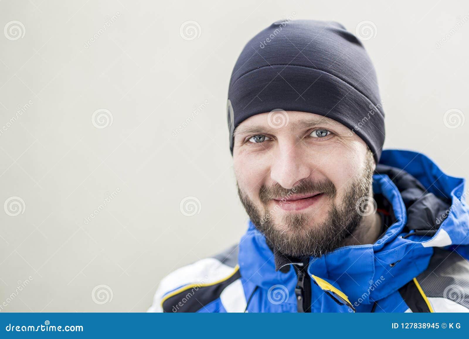 Portret młody dorosły ufny brodaty mężczyzna jest ubranym ciepłego sport odzieżowego i kapeluszowego przy zimnym zima dniem Uśmie