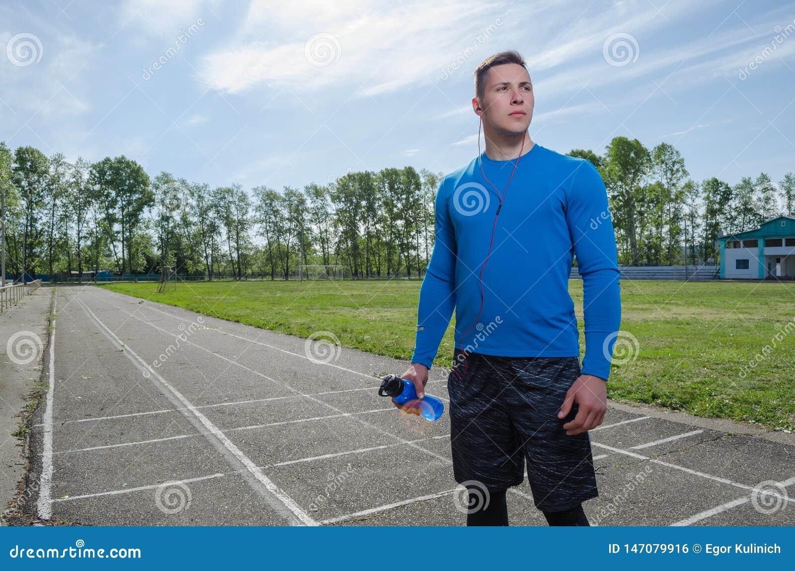 Portret młody jogger w hełmofonach i butelce woda przy stadium