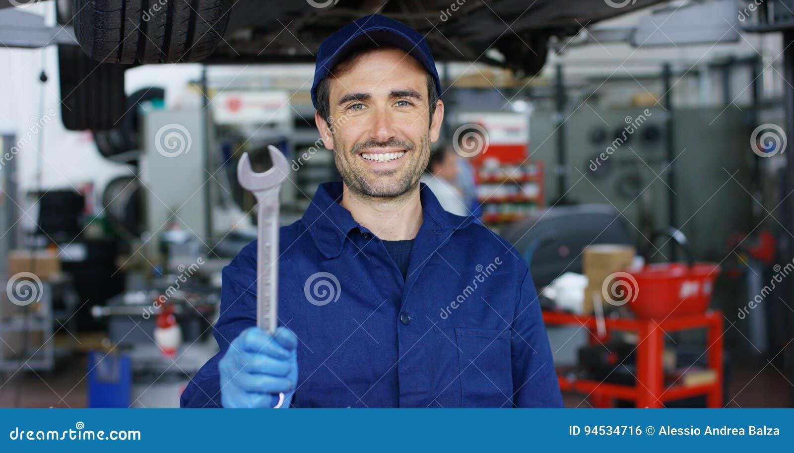 Portret młody piękny samochodowy mechanik w samochodowym remontowym sklepie, ręki z spanner Pojęcie: naprawa maszyny, usterki dia