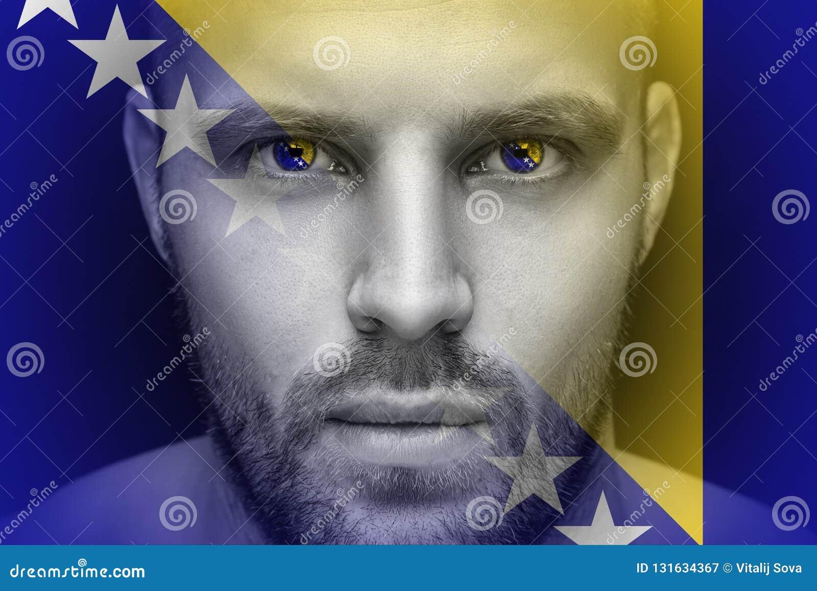 Portret młody poważny mężczyzna, w czyj oczach odbija flaga państowowa