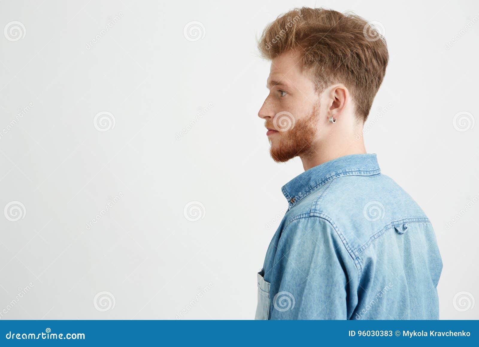 Portret młody przystojny mężczyzna jest ubranym cajgową koszulową pozycję w profilu nad białym tłem z brodą