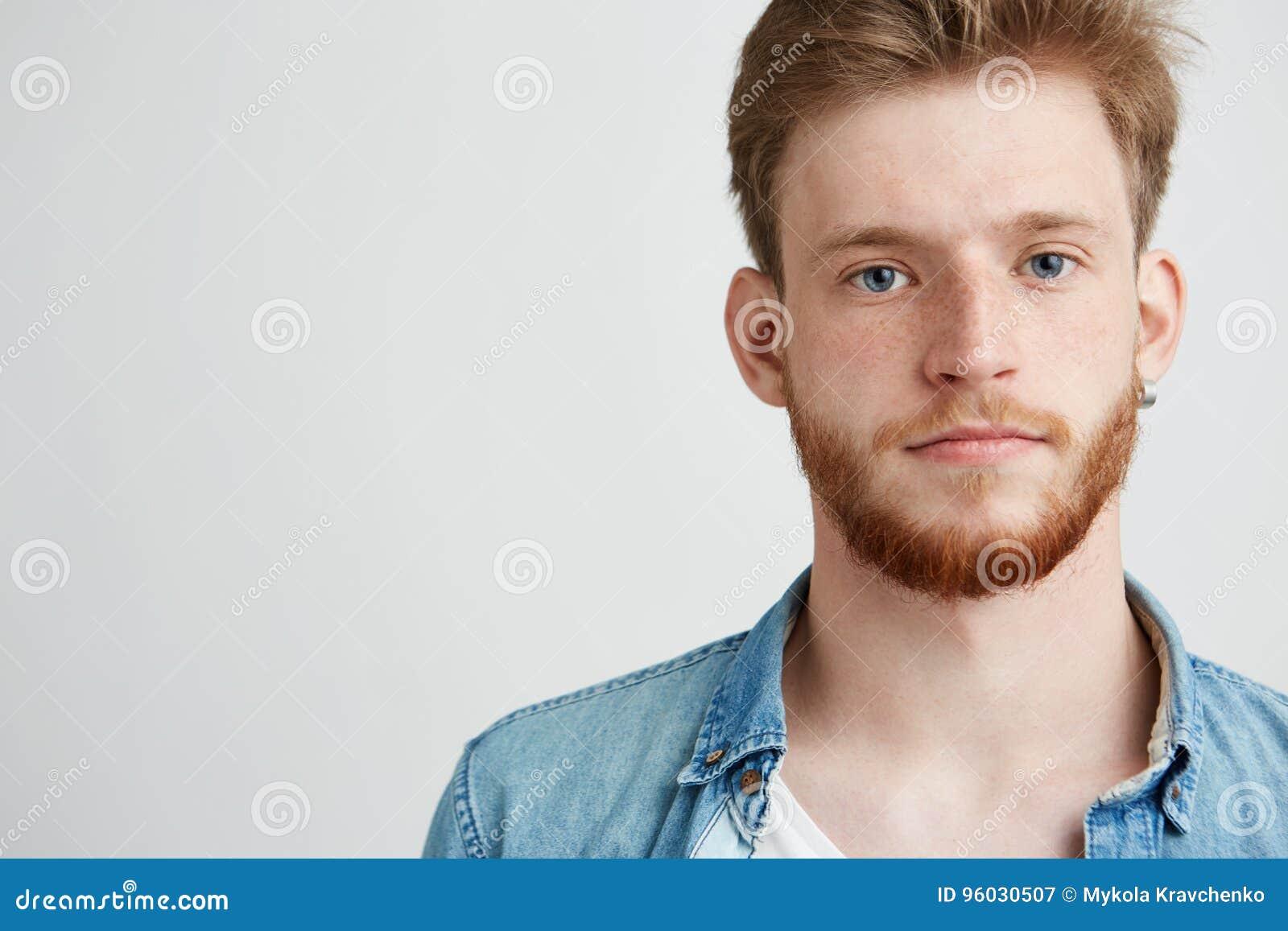 Portret młody przystojny mężczyzna patrzeje kamerę nad białym tłem z brodą