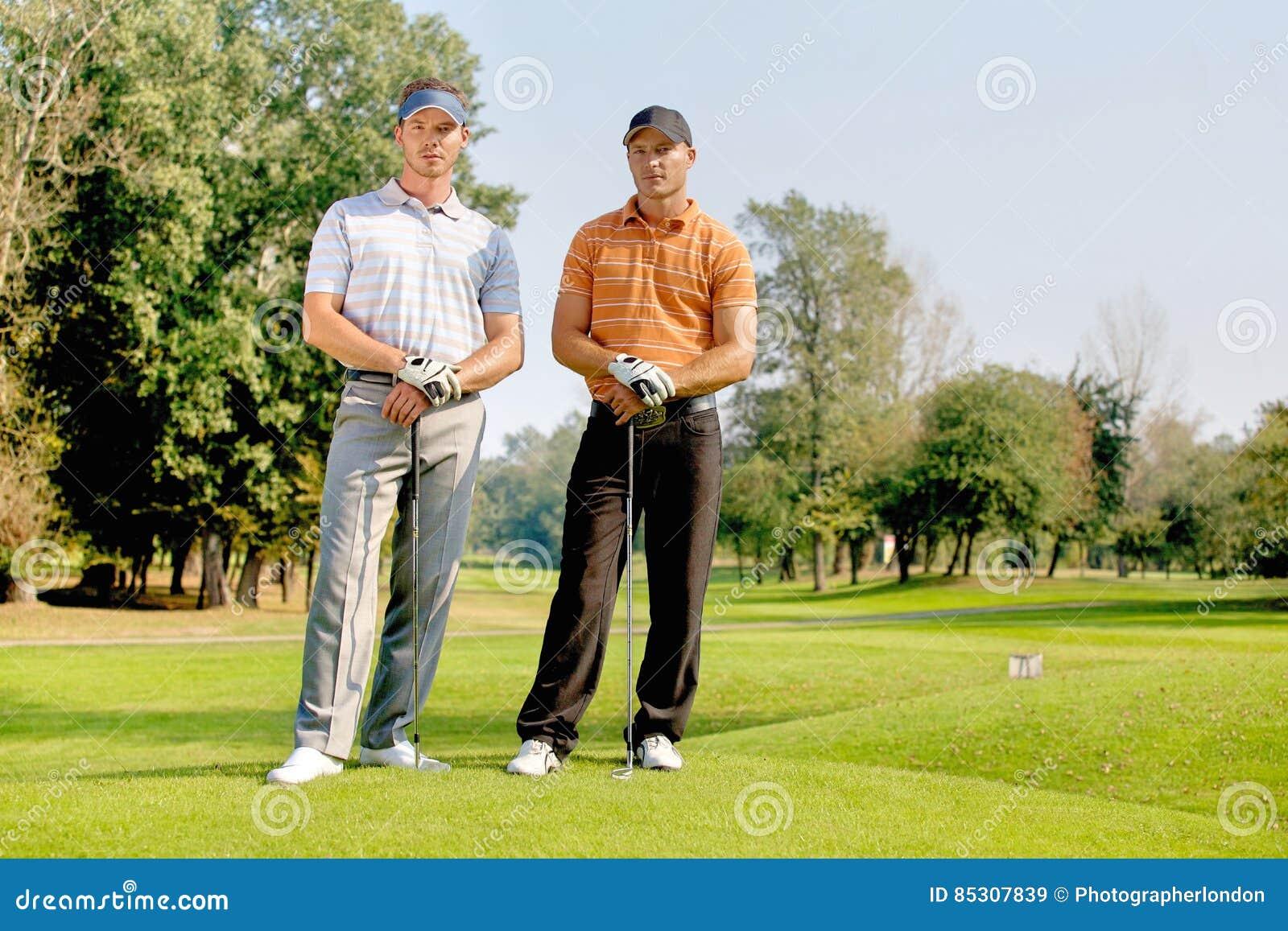 Portret młodzi człowiecy stoi z golfem wtyka na polu golfowym