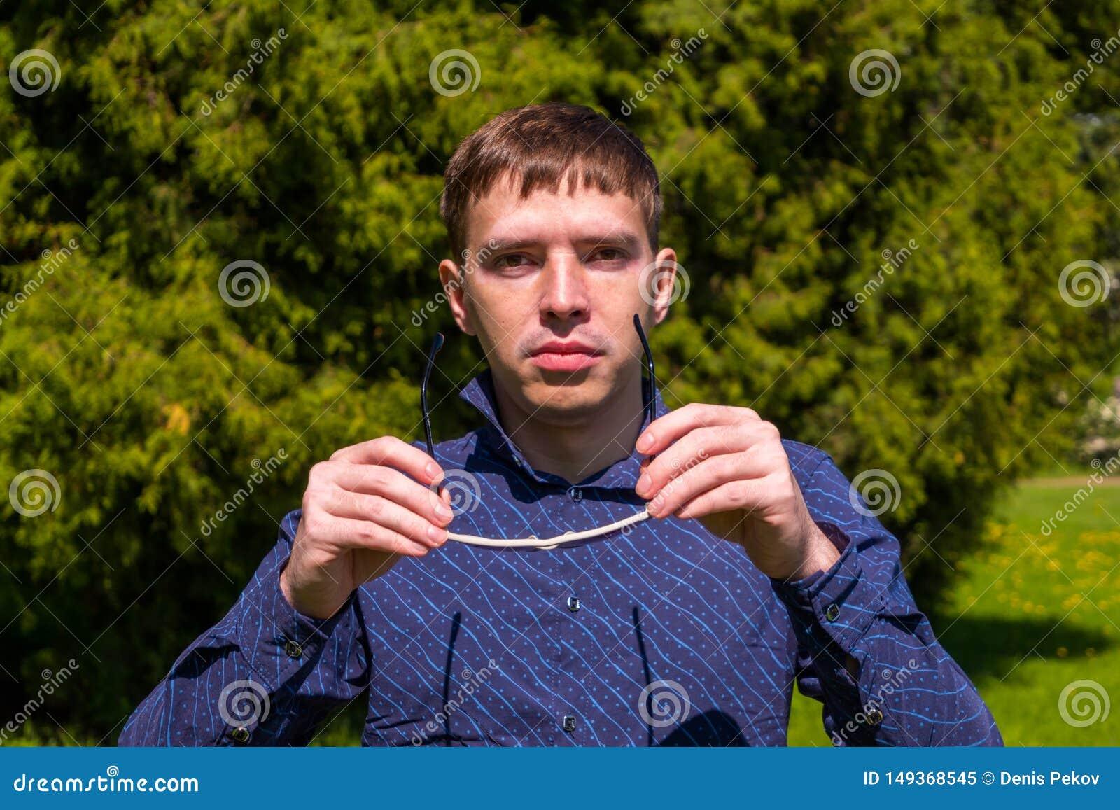 Portret m??czyzna w okularach przeciws?onecznych i b??kitny koszulowy trwanie outside w parku