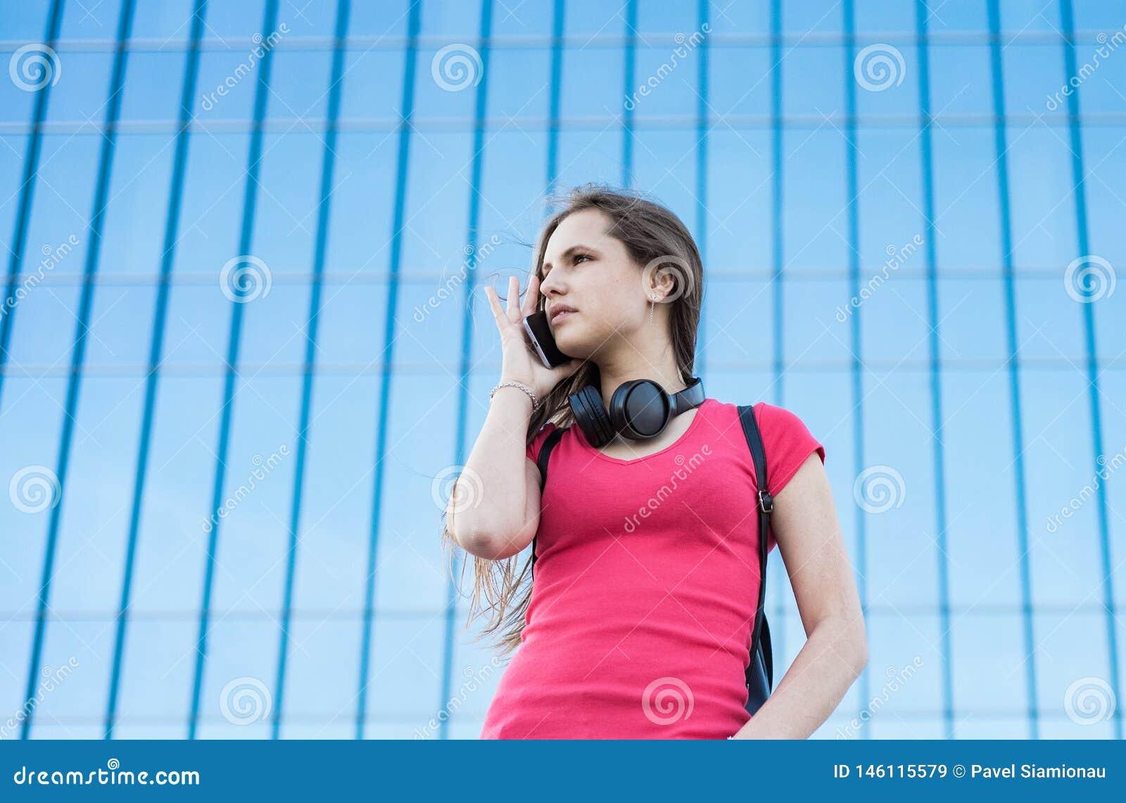 Portret m?oda nastolatek brunetki dziewczyna w koralowej koszulce z d?ugie w?osy dziewczyna na mie?cie opowiada na m?drze telefon