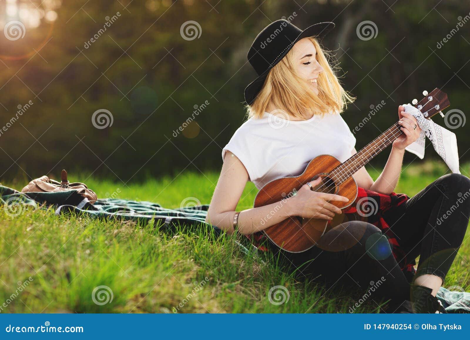 Portret m?oda pi?kna kobieta w czarnym kapeluszu Dziewczyny obsiadanie na bawi? si? gitarze i trawie
