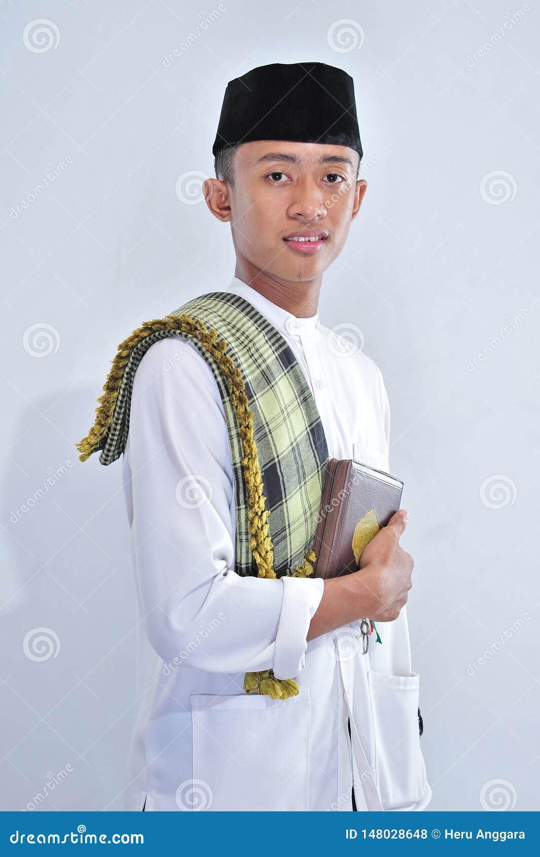 Portret m?ody muzu?ma?ski przewo?enie ?wi?ty koran przy Ramadan kareem