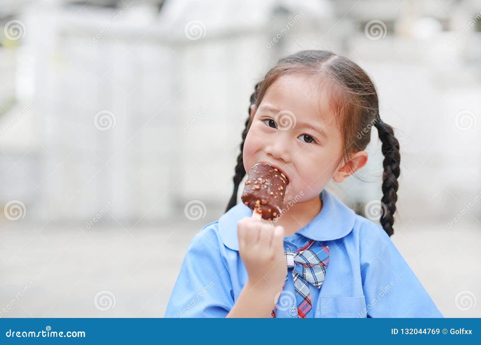 Portret mała Azjatycka dziecko dziewczyna w mundurku szkolnym cieszy się jedzący smakowitego czekoladowego waniliowego lody