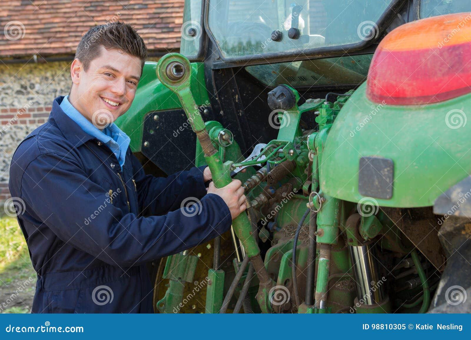 Portret mechanika naprawiania ciągnik Na gospodarstwie rolnym