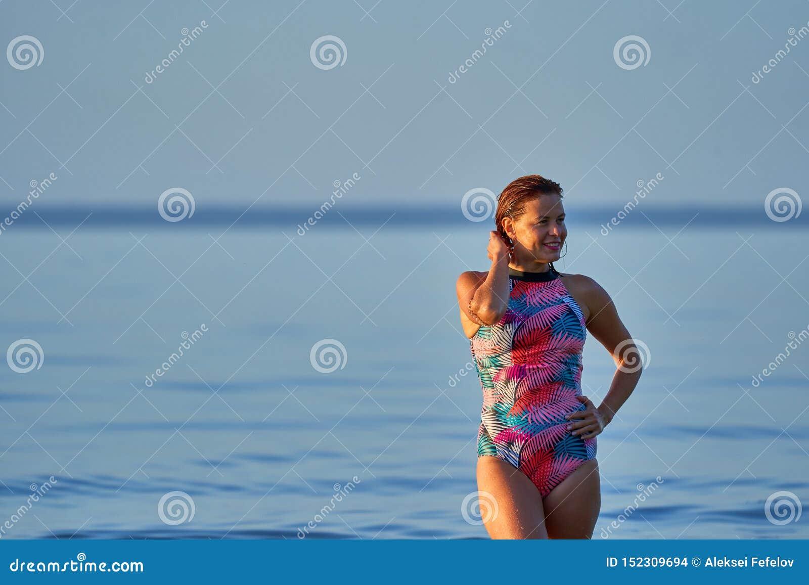 Portret miedzianow?osa mokra w ?rednim wieku kobieta w swimsuit na lato wiecz?r