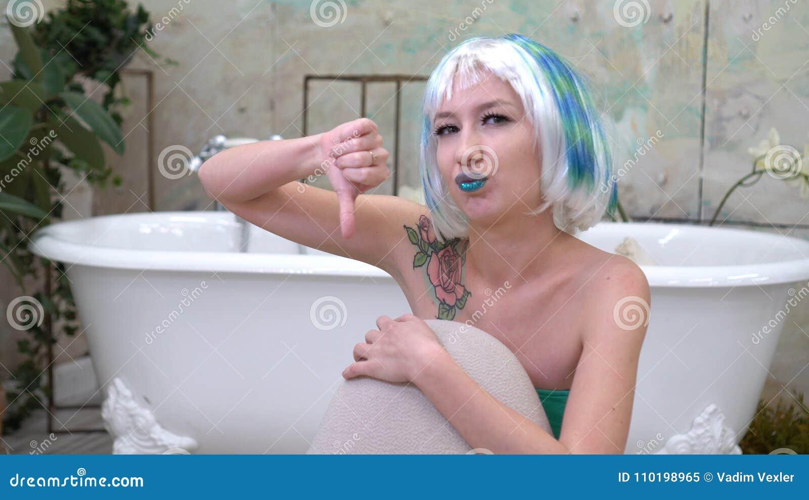 Portret nierada kobieta w peruce która pokazuje kciuka puszek w łazience