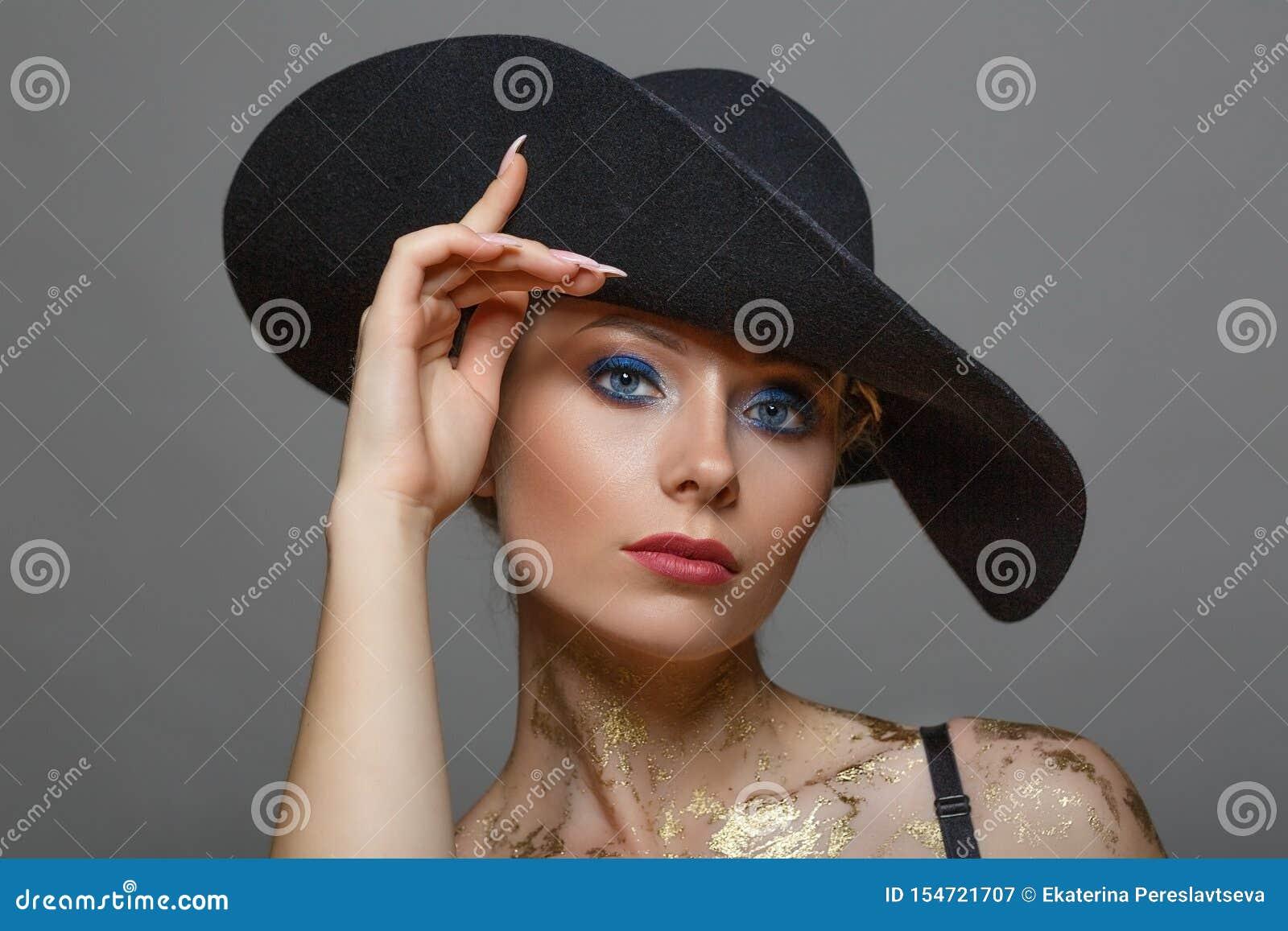 Portret odizolowywający piękna kobieta wewnątrz z makijażem w czarnym kapeluszu na białym tle,