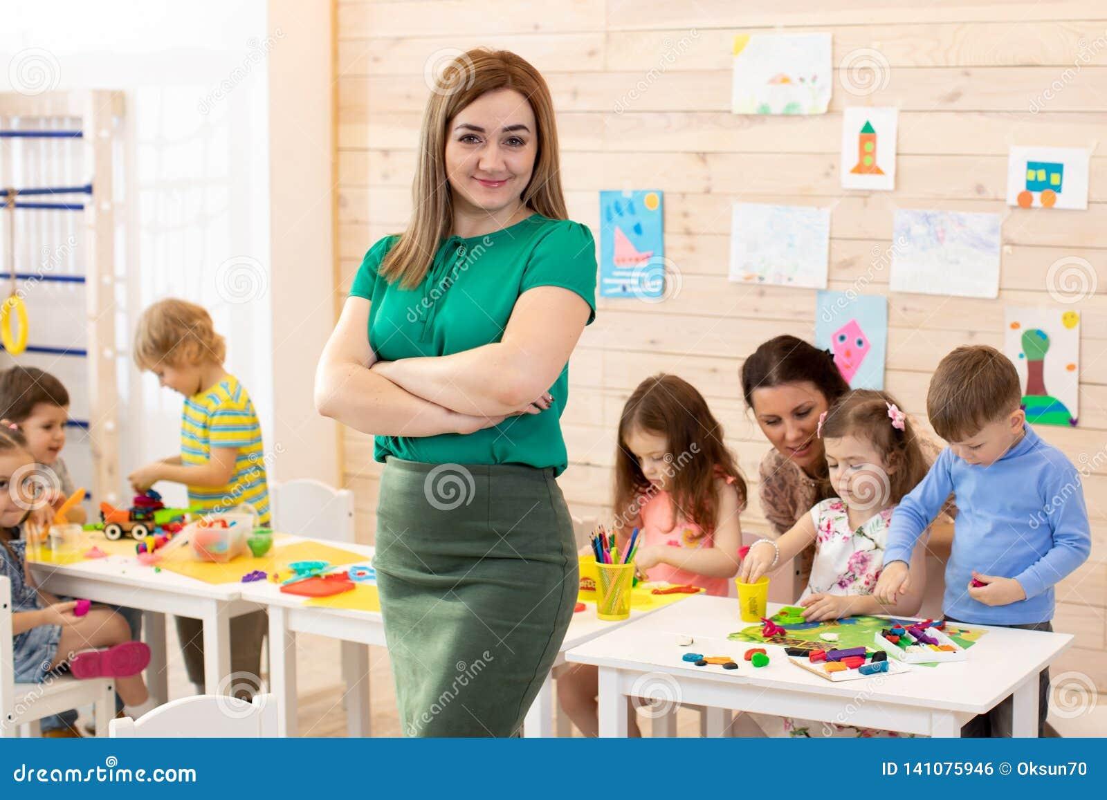 Portret ono uśmiecha się przy kamerą i dzieciakami studiuje przy preschool żeński nauczyciel
