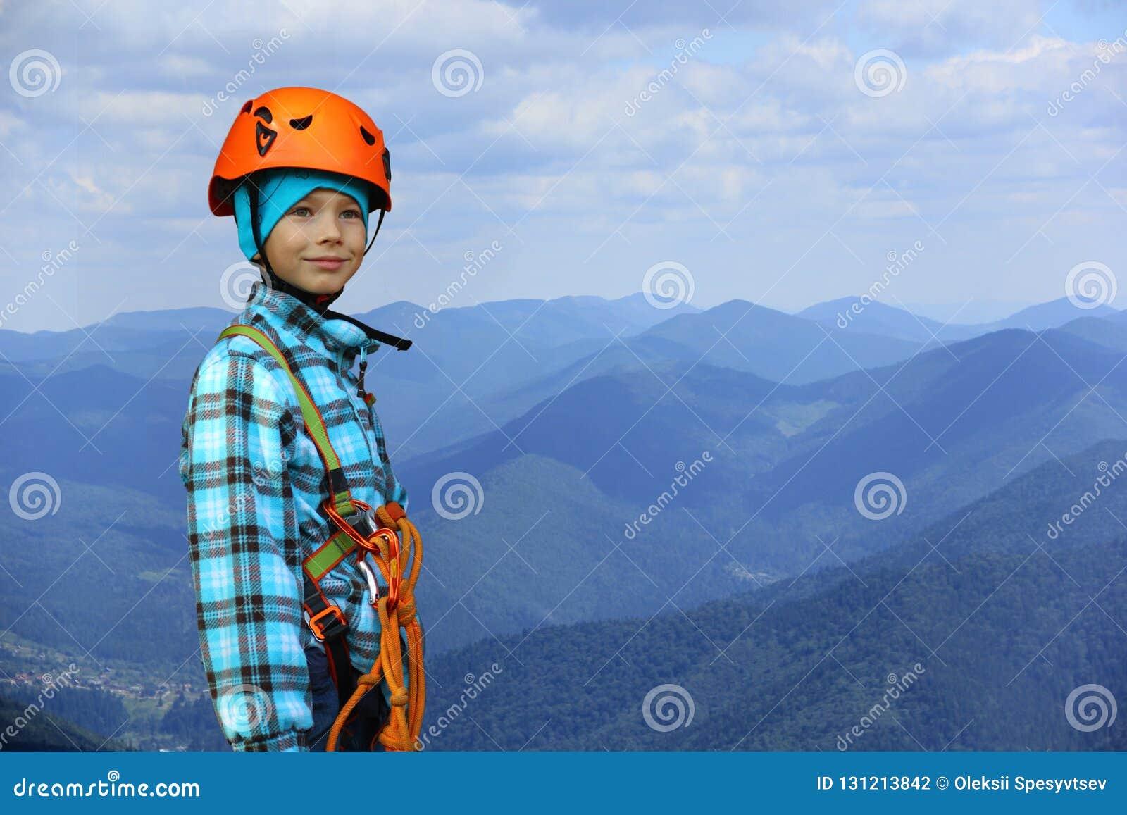 Portret ono uśmiecha się sześć roczniaków chłopiec jest ubranym hełma i pięcia zbawczą nicielnicę w górach