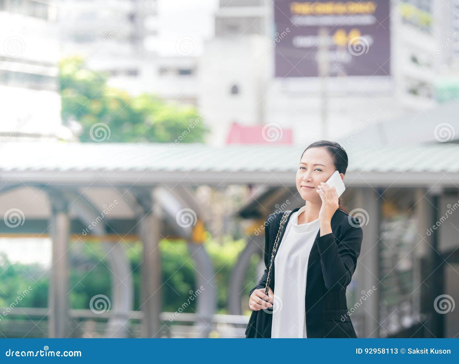 Portret opowiada na smartphone i śmia się outdoors rozochocona młoda kobieta piękna aisan biznesowa kobieta używa telefon komórko