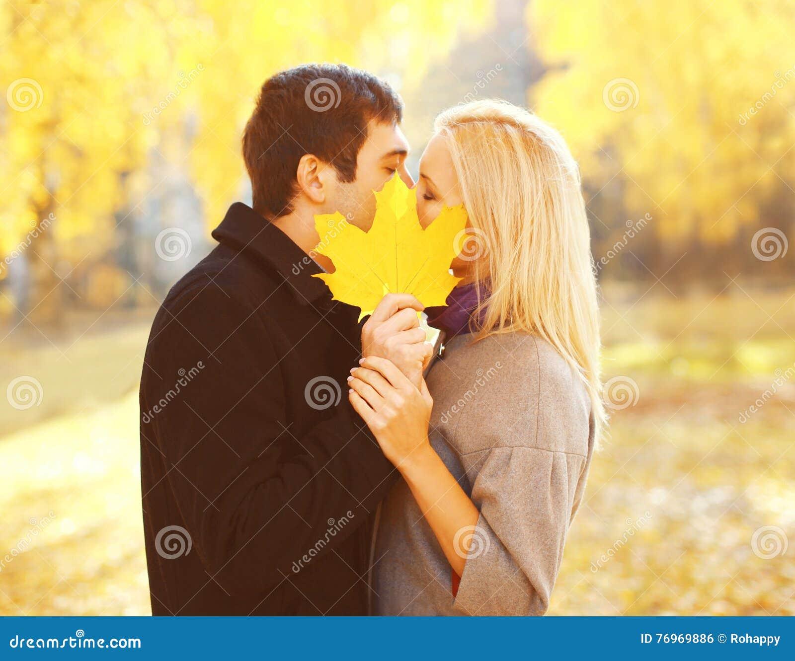 Portret pary młodego kochającego całowania końcowy żółty liść klonowy w ciepłej pogodnej jesieni