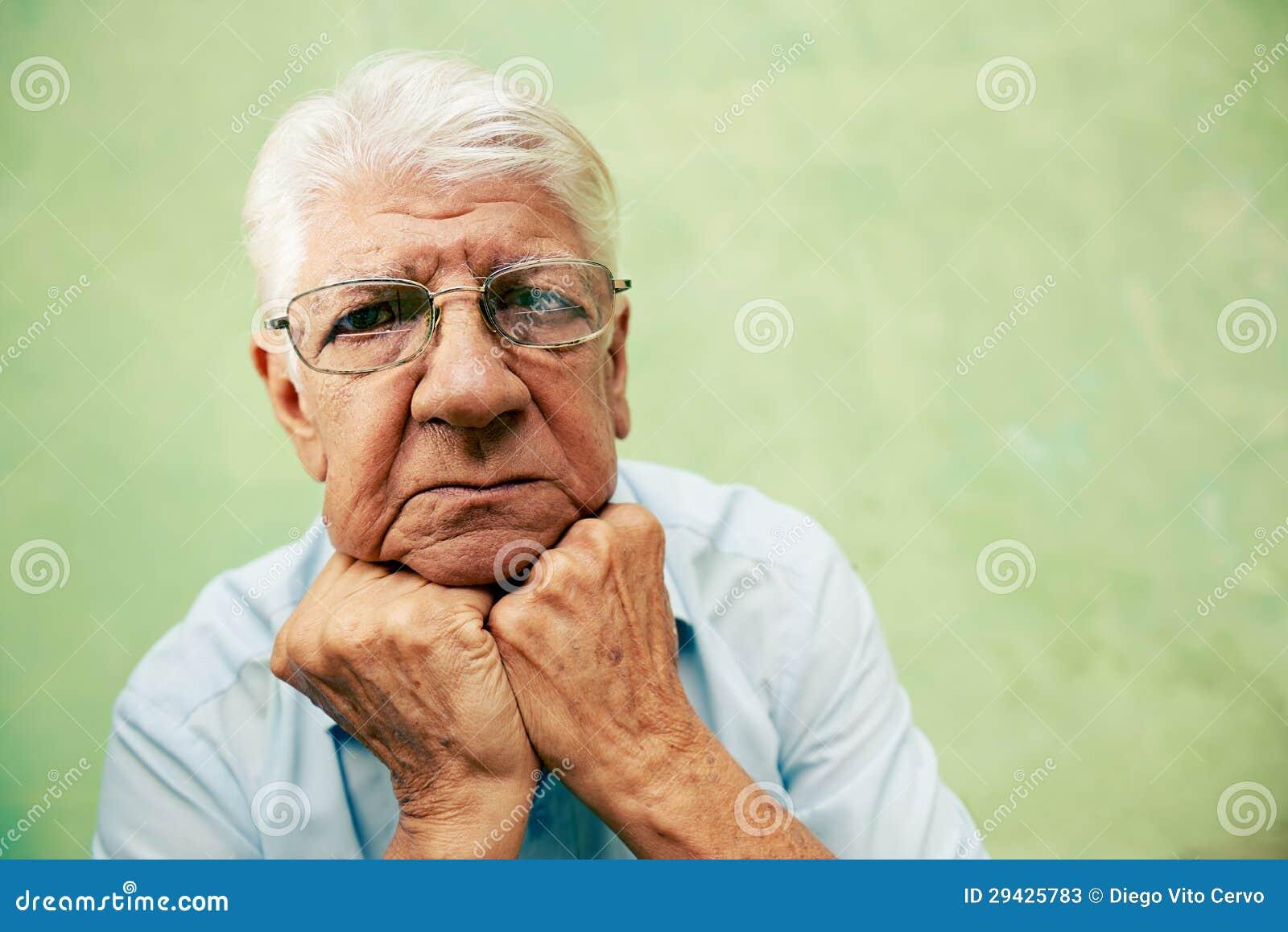 Portret patrzeje kamerę z rękami na podbródku poważny stary człowiek