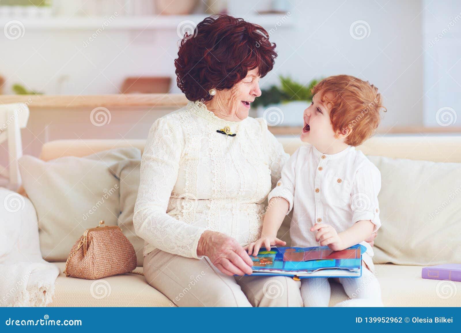 Portret piękna dojrzała kobiety 80 lat dama z jej wnukiem w domu, czyta edukacyjną książkę wpólnie