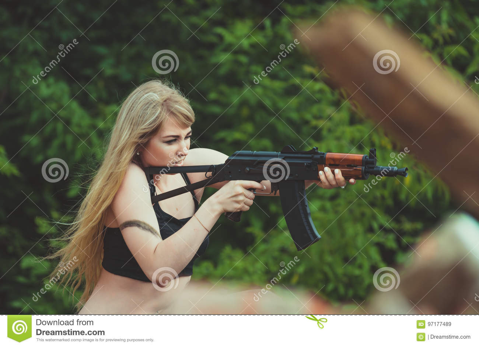 Portret piękna dziewczyna w kamuflażu w jej rękach podczas a