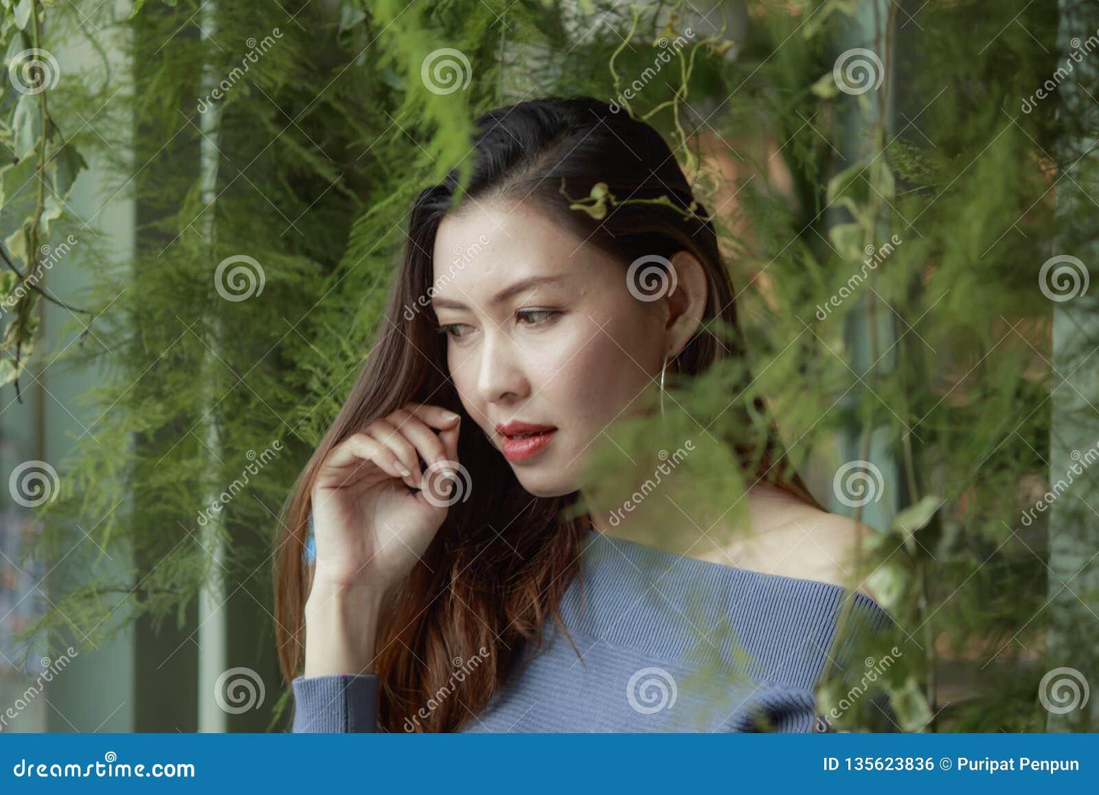 Portret piękna kobieta pod liści patrzeć