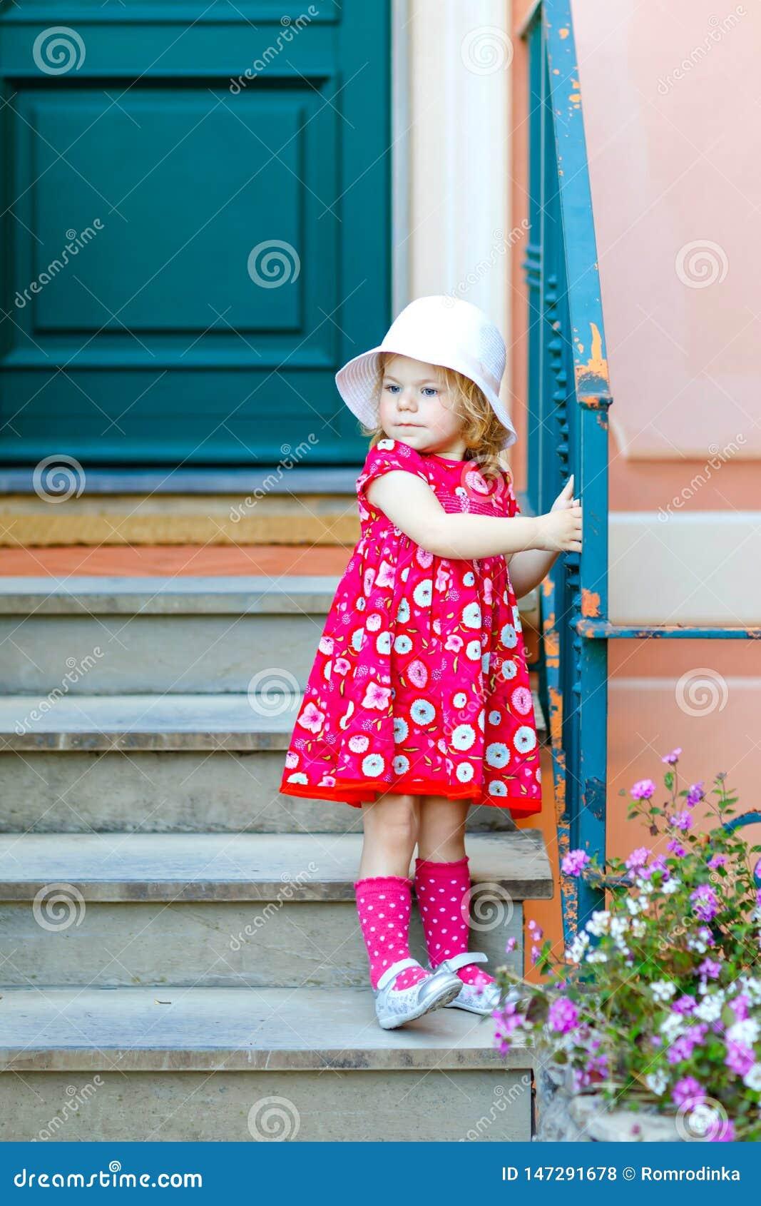 Portret piękna mała berbeć dziewczyna w różowych lata spojrzenia ubraniach, mody sukni, kolanowych skarpetach i kapeluszu, Szcz??