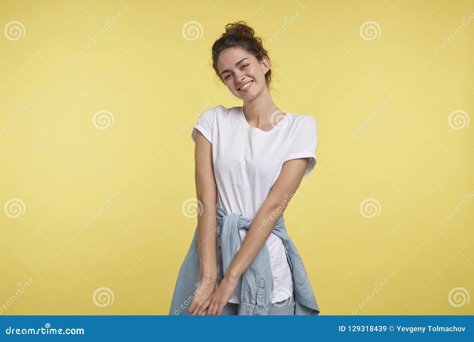 Portret piękna nieśmiała studencka dziewczyna odizolowywająca nad żółtym tłem