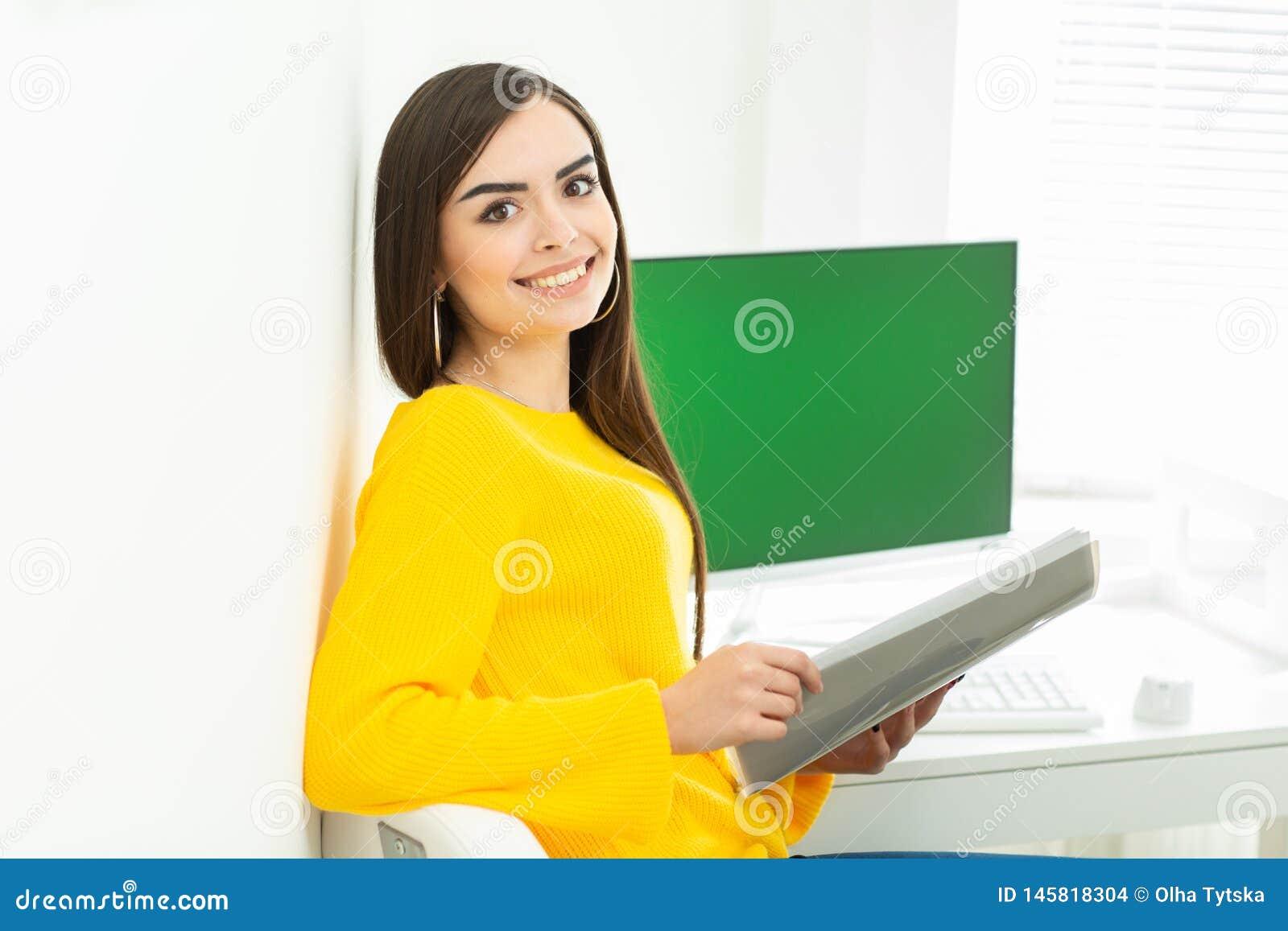 Portret piękna uśmiechnięta kobieta pracuje na jej biurku z zieleń ekranem w biurowym środowisku,