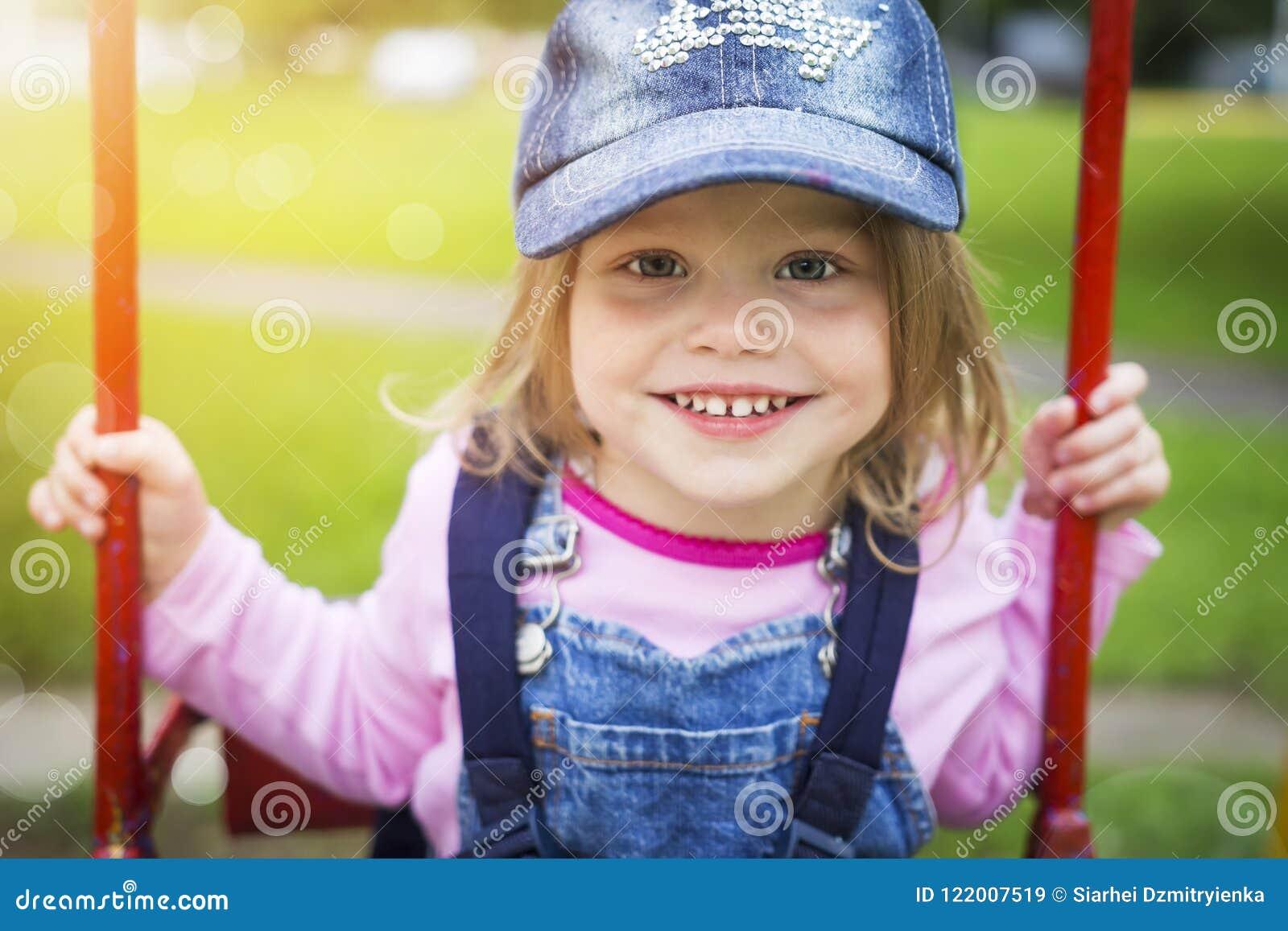 Portret piękna uśmiechnięta mała dziewczynka w lato parku na huśtawce Szczęśliwy śliczny dziecko jedzie na huśtawce