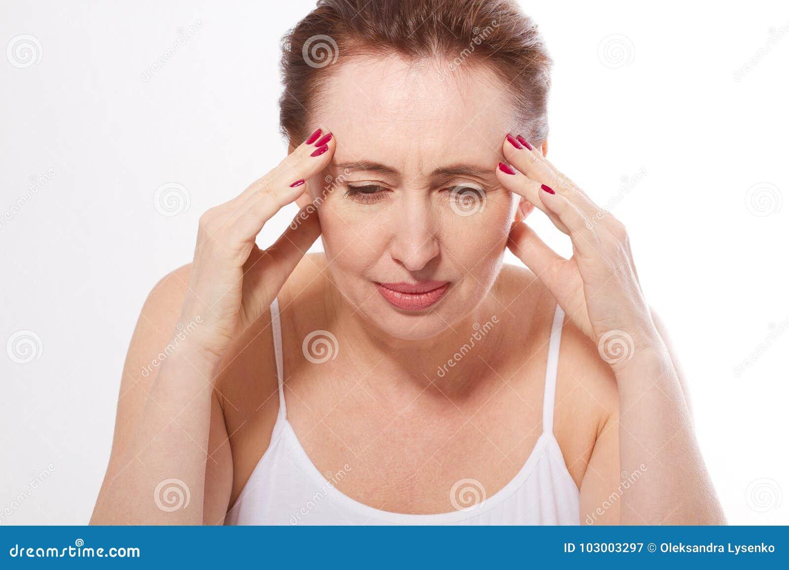 Portret piękna w średnim wieku brunetki kobieta z migreną na bielu Migrena, przekwitanie i stres, Odbitkowa przestrzeń i m