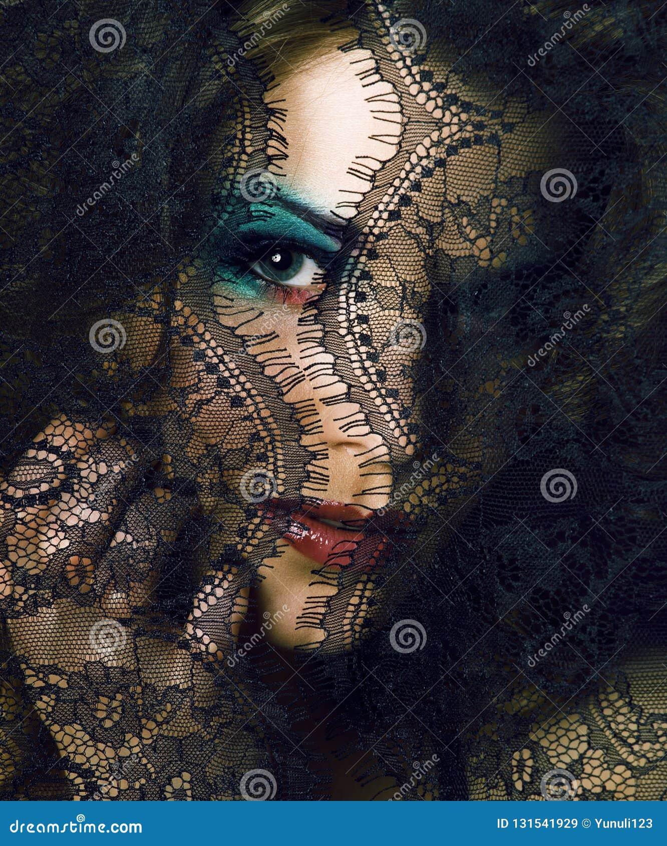 Portret piękno młoda kobieta przez koronki zakończenia w górę tajemnicy mak