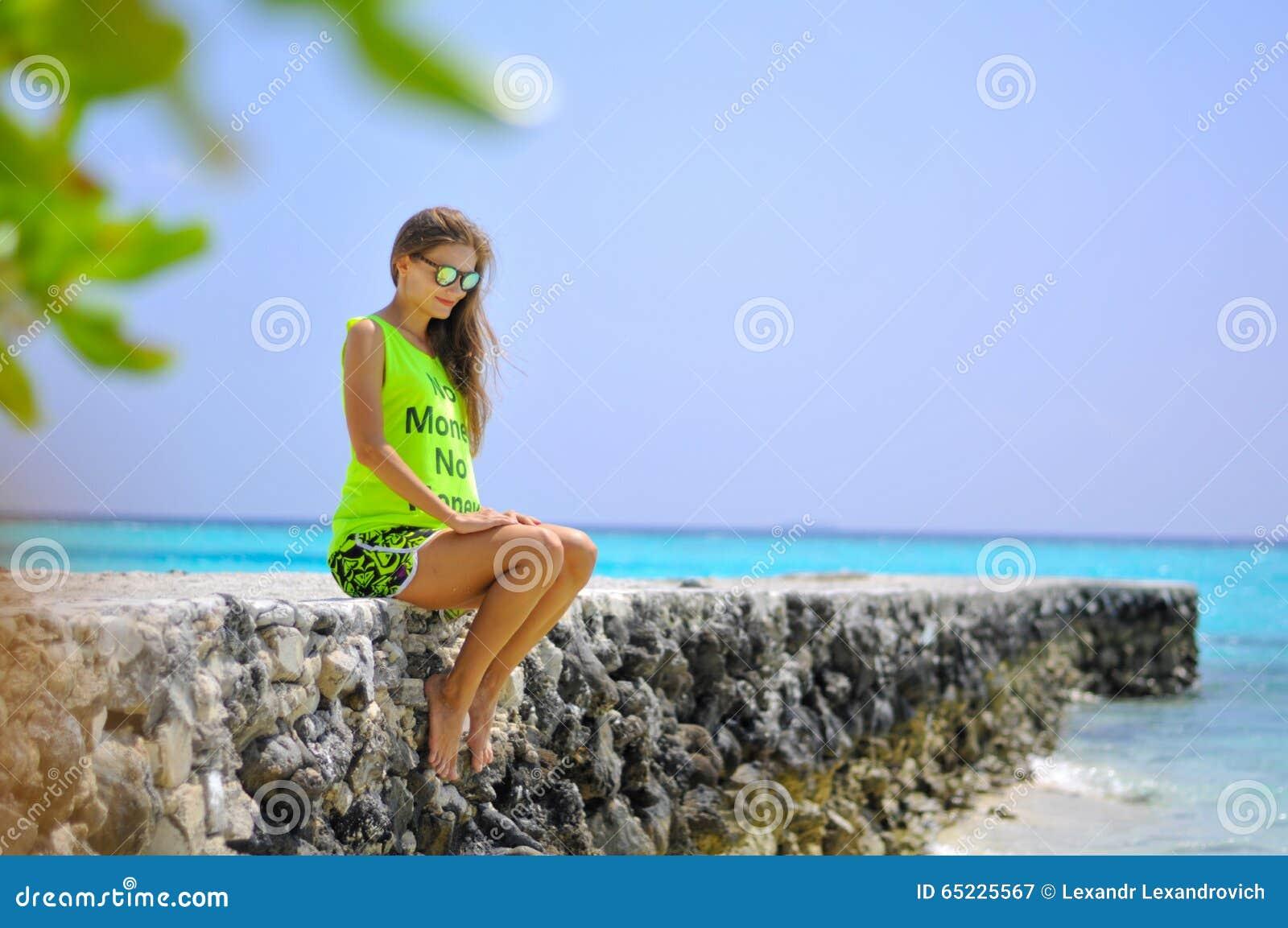 Portret piękny dziewczyny obsiadanie na molu przy tropikalną plażą