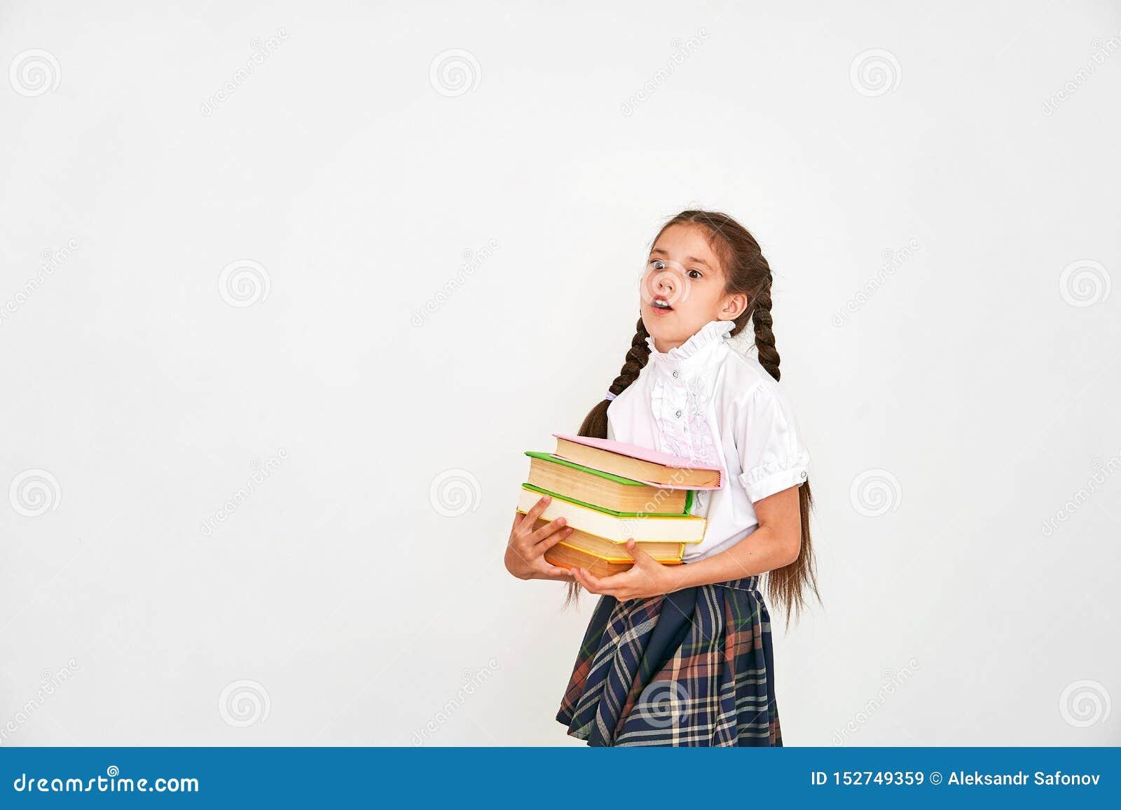 Portret piękny mała dziewczynka uczeń ono uśmiecha się na białym tle z plecakiem i sterta książki w jego rękach