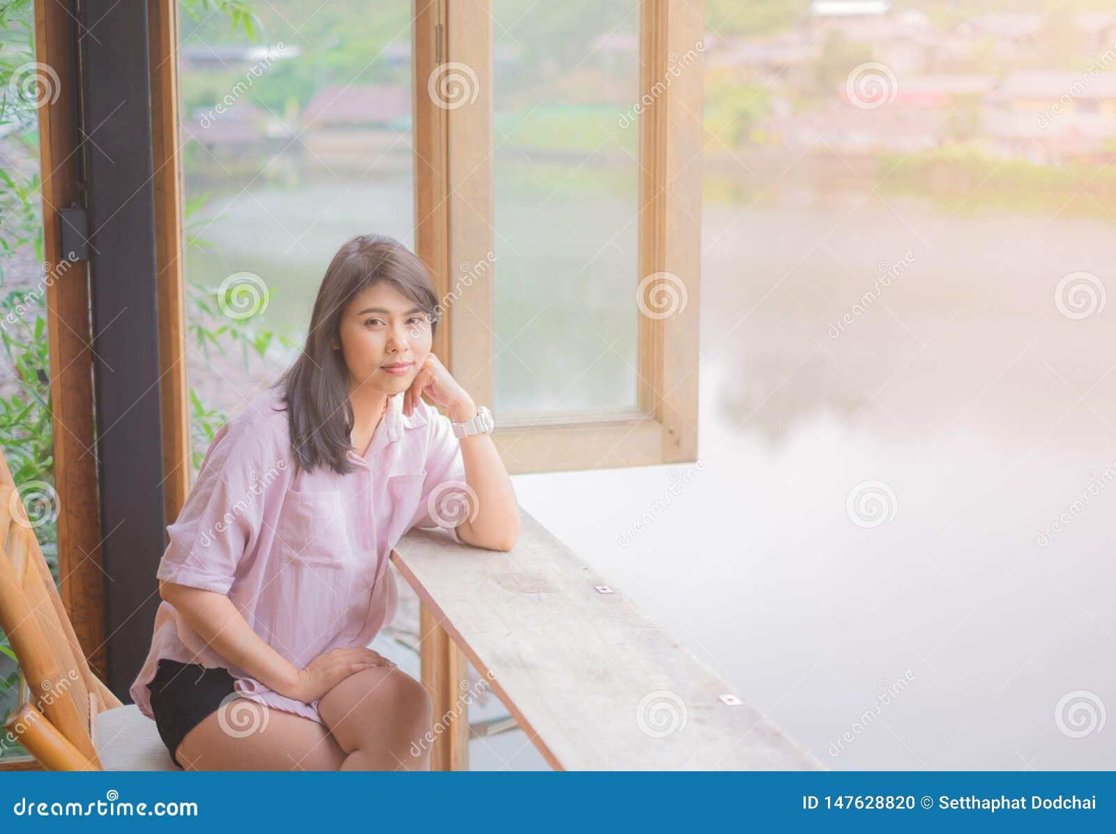 Portret pi?kna azjatykcia kobieta siedzie? na drewnianym krze?le st?? blisko okno