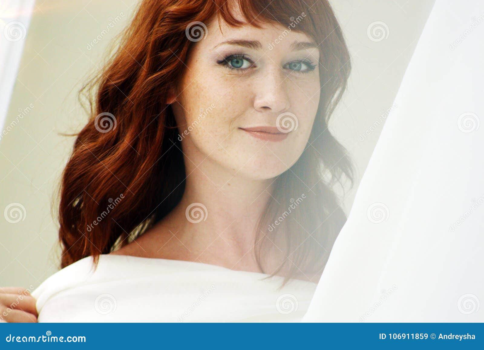 Portret piękna redheaded kobieta patrzeje flirciarski