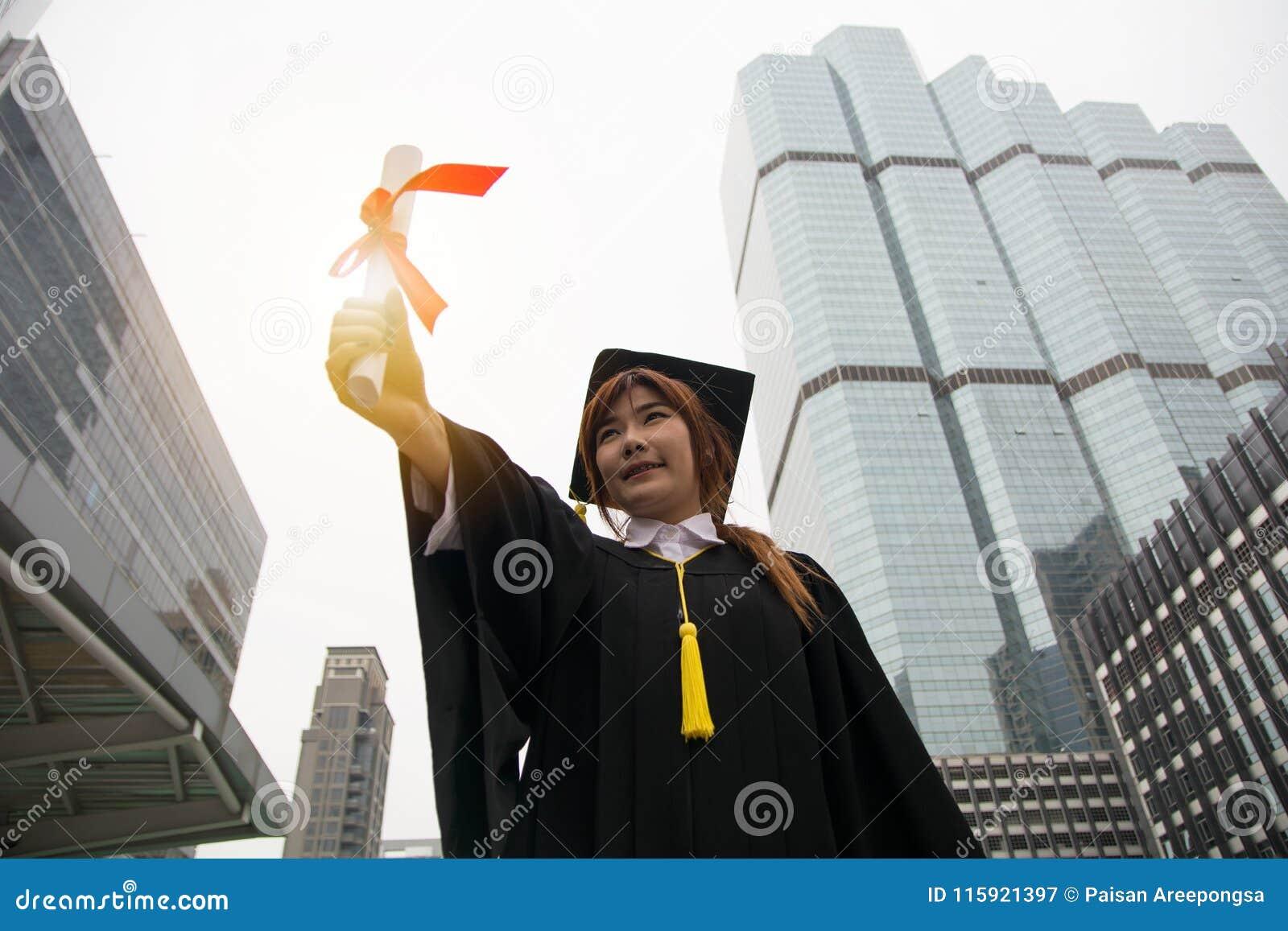 Portret pomyślny magisterski żeński uczeń jest ubranym nakrętkę i g