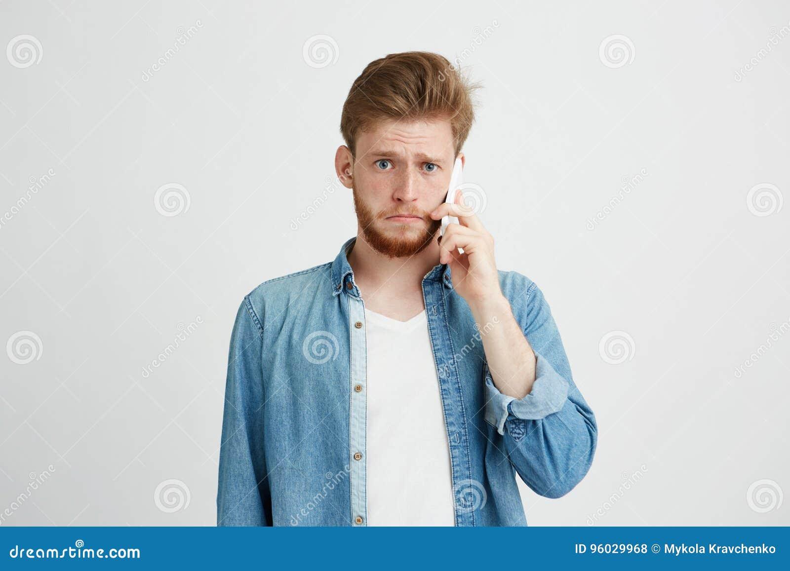 Portret potomstwa spęczenia mężczyzna opowiada na telefonie patrzeje kamerę nad białym tłem
