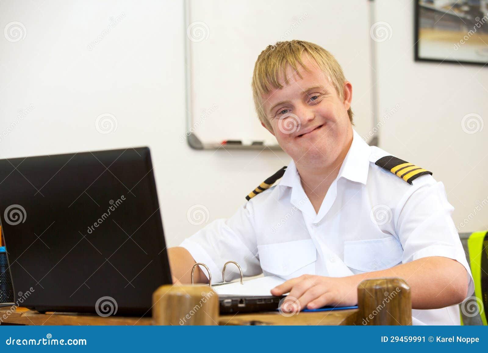 Portret potomstwo pilot z puszka syndromem przy biurkiem.