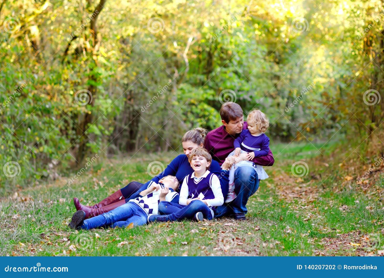 Portret potomstwo rodzice z trzy dziećmi Matka, ojciec, dwa dzieciaków braci chłopiec i małej ślicznej berbeć siostra,