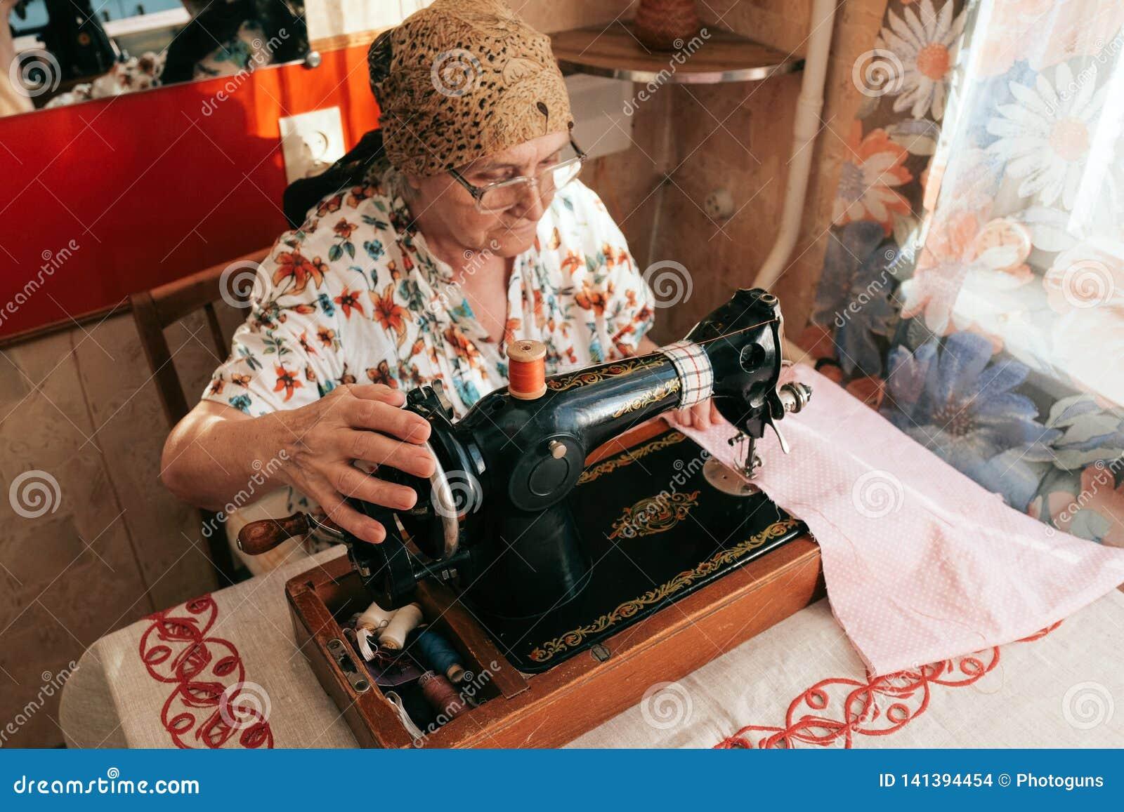 Portret pracuje od domu 70 lat starsza kobieta w widowiskach używać szwalną maszynę, Praca dla starych starzejących się ludzi, od