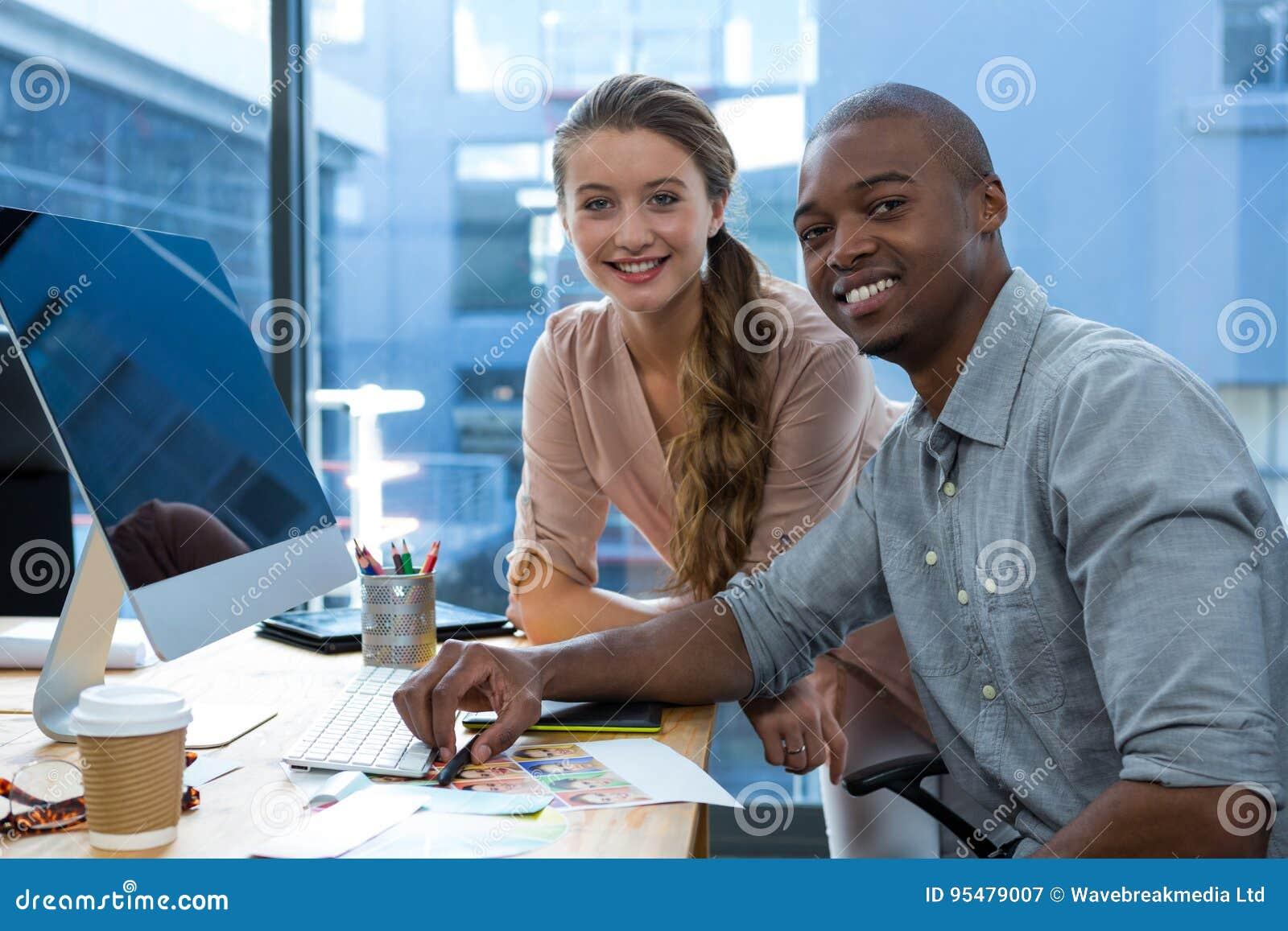 Portret projektant grafik komputerowych przy biurkiem z kolegą