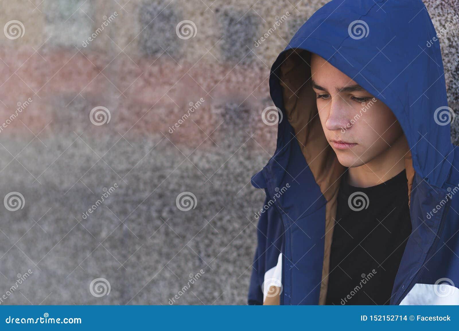 Portret przygnębiony smutny nastoletni chłopak na ciemnym tle, nastoletni problemowy pojęcie