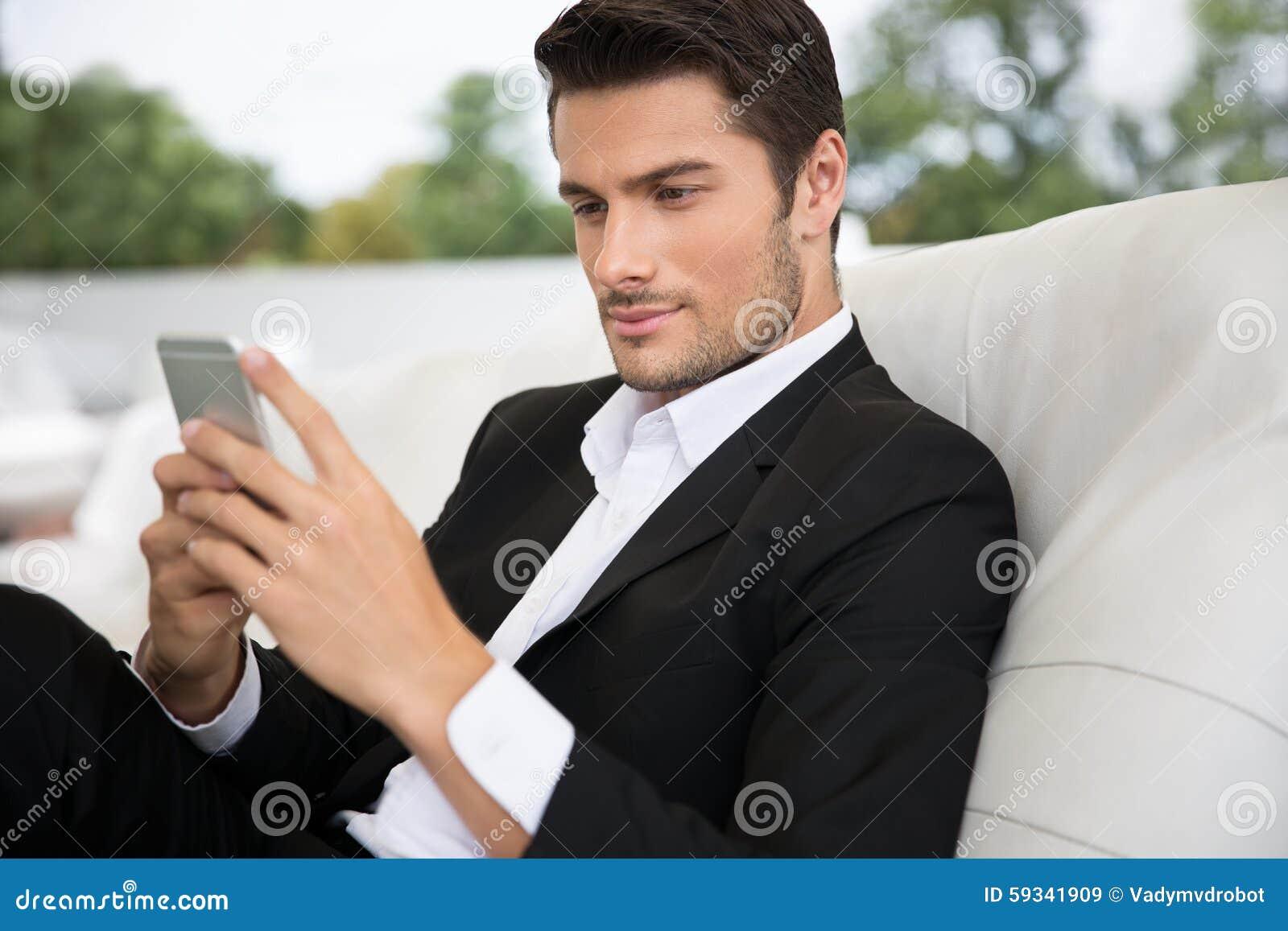 Portret przystojny mężczyzna używa smartphone