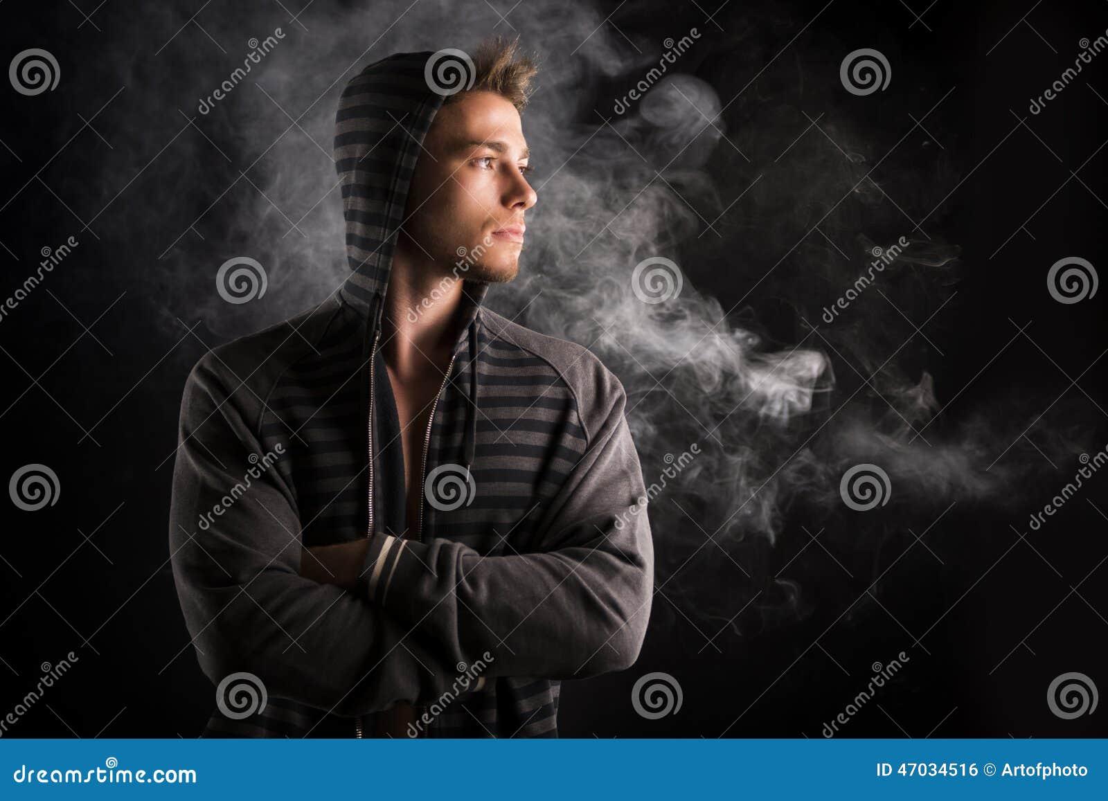 Portret przystojny twardy młody człowiek w ciemnym hoodie