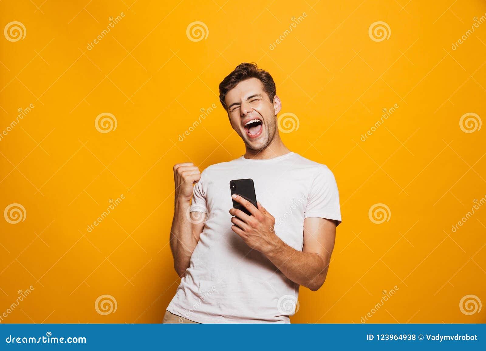Portret radosny młodego człowieka mienia telefon komórkowy