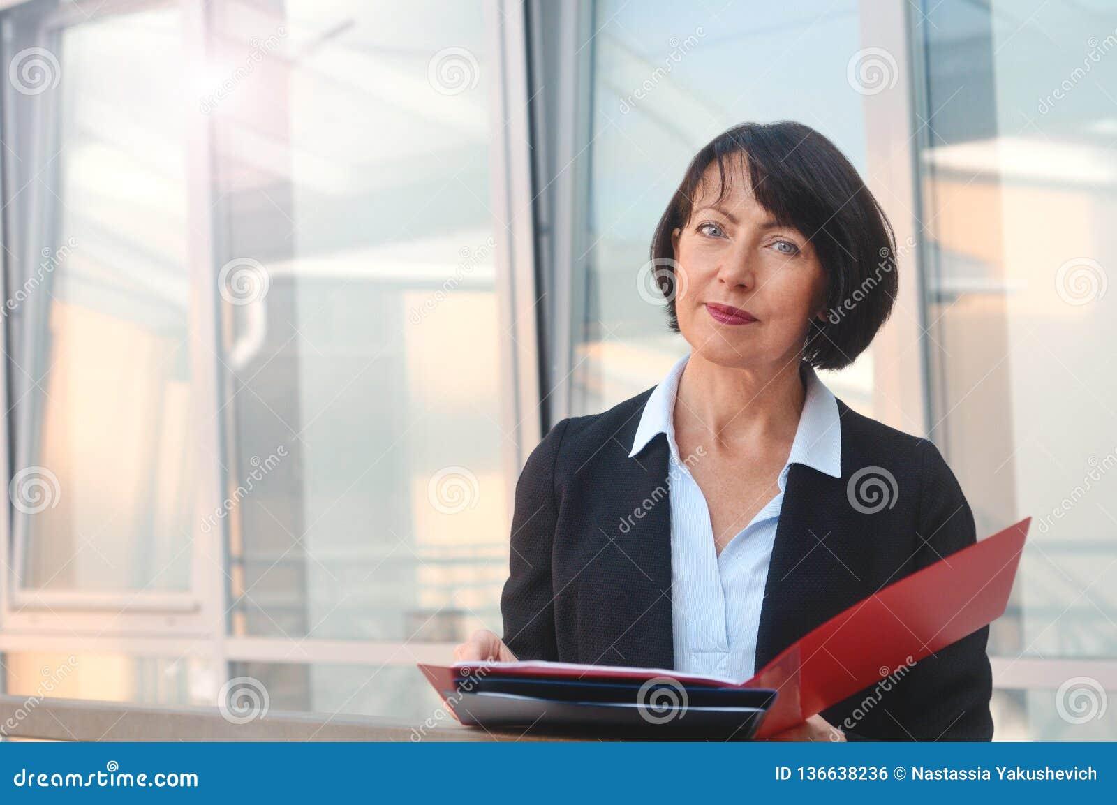 Portret rijpe bedrijfsvrouw met een omslag van documenten