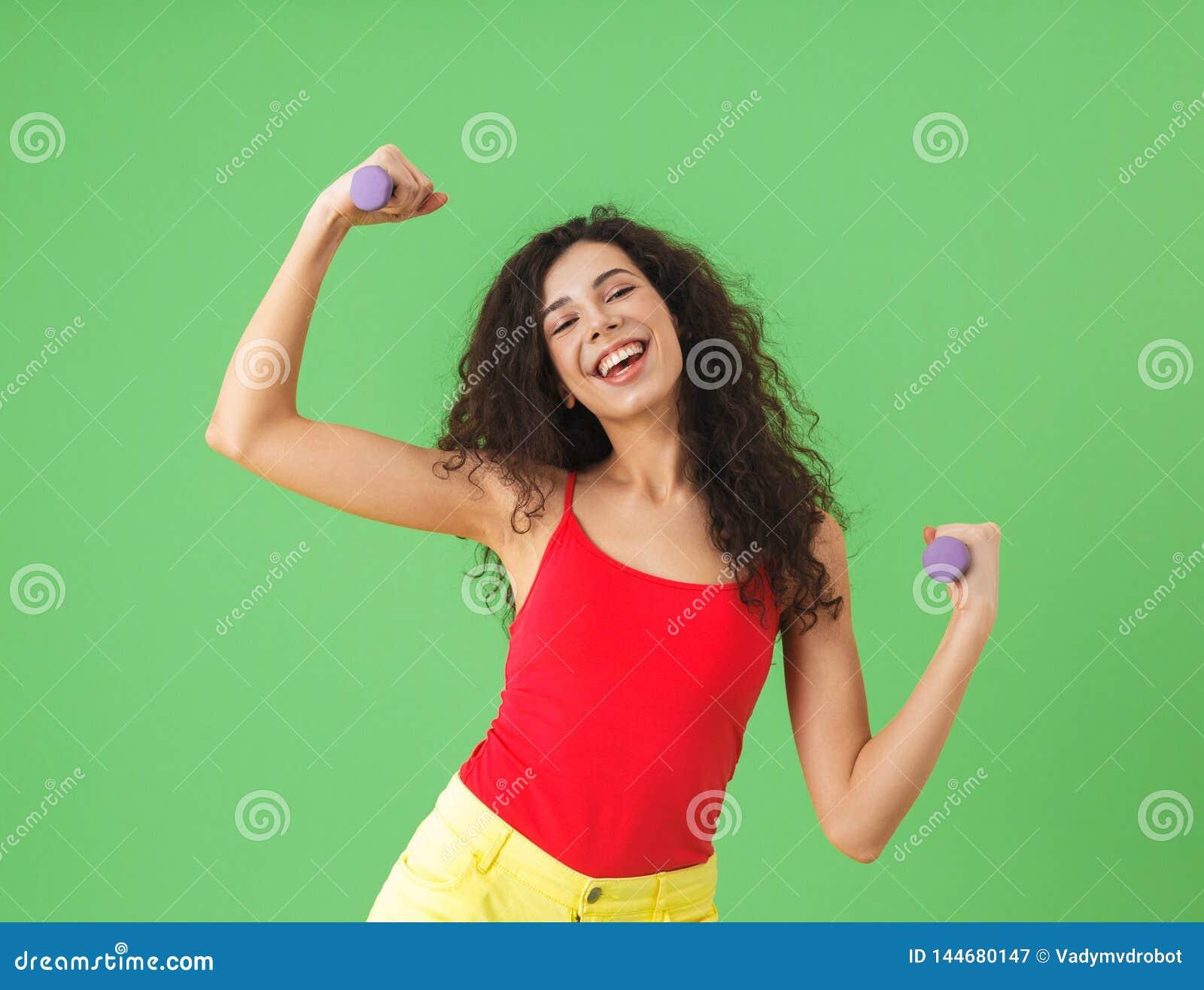 Portret robi sportom i udźwigów ciężarom przeciw zieleni ścianie caucasian dziewczyna