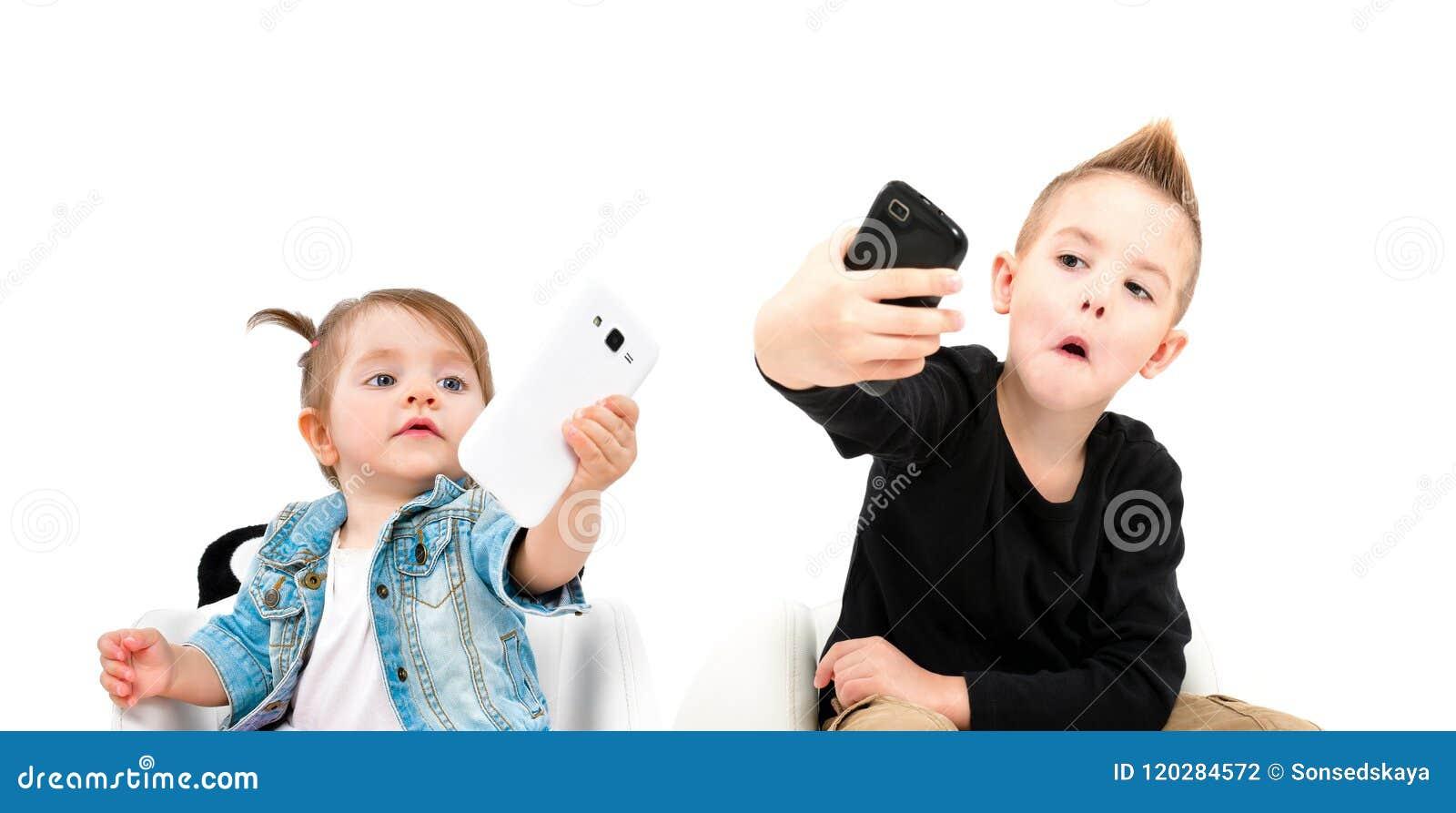Portret rozochocona chłopiec i śliczna dziewczyna bierze selfie na telefonie komórkowym