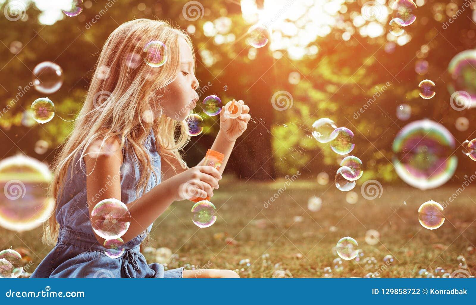 Portret rozochocona dziewczyna dmucha mydlanych bąble