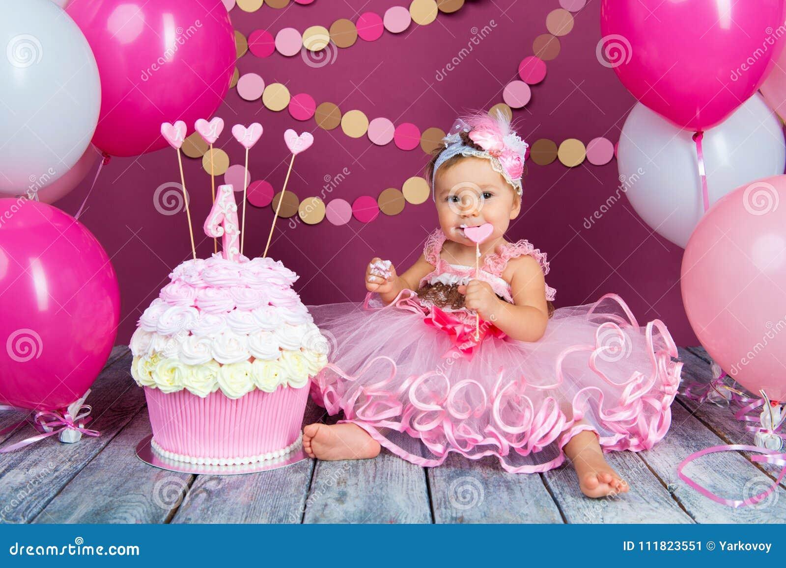 Portret rozochocona urodzinowa dziewczyna z pierwszy tortem troszkę Jeść pierwszy tort Roztrzaskanie tort